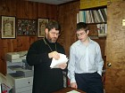 Zachary works with Fr. John on his prayer book.