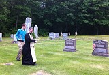Fr. John, assisted by his son, Peter, blesses the graves in the Parish Cemetery